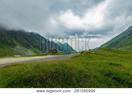 Transfagarasan Road In Stormy Weather. Popular Travel Destination Of Romania. Grassy Meadow Along On