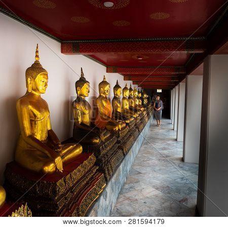 Tourist Looks At Row Of Golden Buddha Statues Wat Pho Palace Thailand Bangkok
