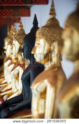 Row Of Golden Buddha Statues Wit Focus On Black Buddha Wat Pho Palace Thailand Bangkok