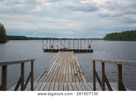 Wooden Jetty On The Lake. Alexander-svirsky Monastery Is Placed Near The Lake. People Staying Near T