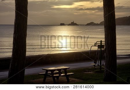 Daybreak At Swansea Bay Promenade Showing A Picnic Bench At West Cross, A Calm Sea And A View Of Mum