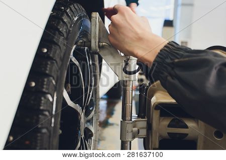 A Car On The Car Steering Wheel Balancer And Calibrate With Laser Reflector Attach On Each Tire To C