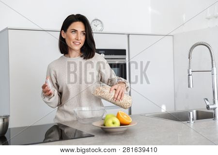 Image of adult woman 30s making breakfast with oatmeal and fruits while standing in modern kitchen at home poster