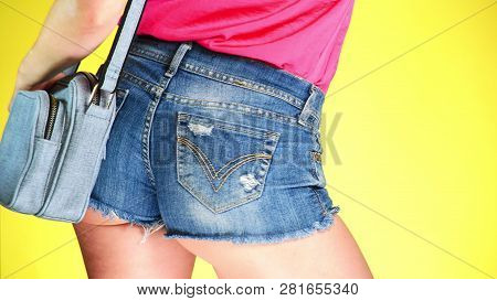 Girl in denim shorts with fashion accessories. denim reticule. Summer fresh style. colored yellow background poster