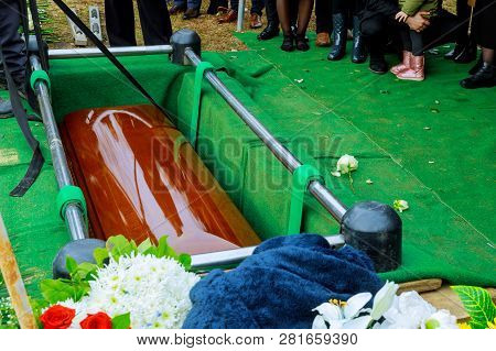 People At Funeral Putting Down The Coffin At A Funeral