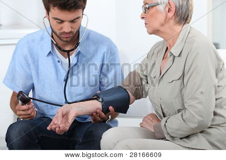 Doctor taking the blood pressure of a patient