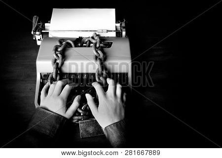 Information censorship - Hands writing on a typewriter locked with a chain and padlock