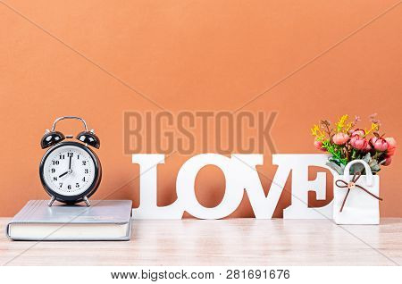 Wooden Love Text On Desk Space And Black Alarm Clock With Notebook On Wooden Background.