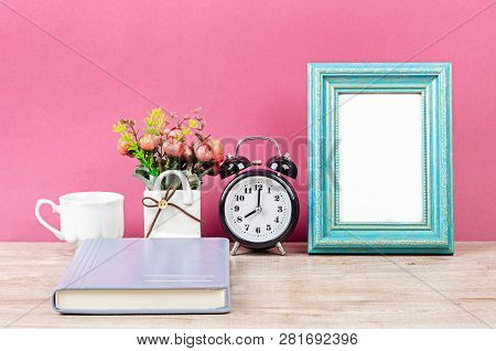 Blank Photo Frame On Desk Space With Notebook On Pink Background.