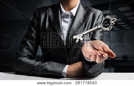 Cropped Image Of Businessman In Suit Keeping Big Key In Hand With Office View On Background.