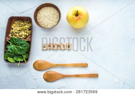 Spinach, pumpkin seeds, sesame, apple and two wooden spoons on a white background. Anemia concept. Close-up. poster