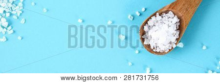 Crystals Of Large Sea Salt In A Wooden Spoon On A Blue Table