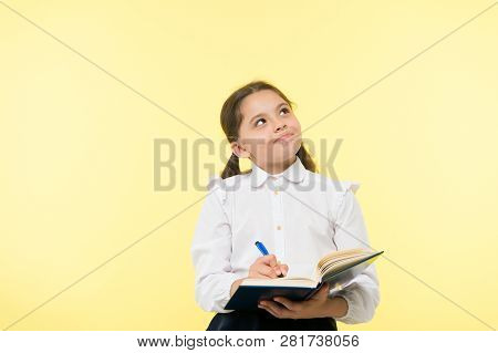 Child School Uniform Kid Doing Homework. Child Girl School Uniform Clothes Hold Book And Pen. Girl C