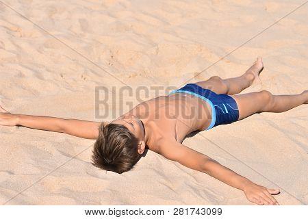 Teen Lies In The Sand On Sea Beach, Angel