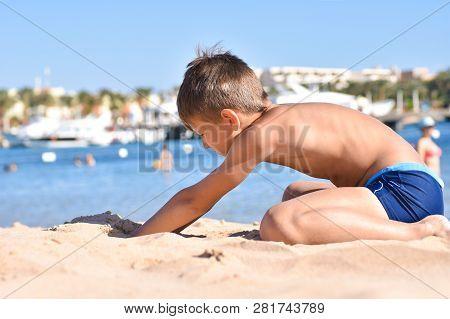 Teen Plays In The Sand On  Sea Beach