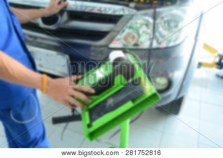 The Blurred Of The Mechanic In Blue Uniform Use The Green Battery Testing Tool In Front Of The Grey