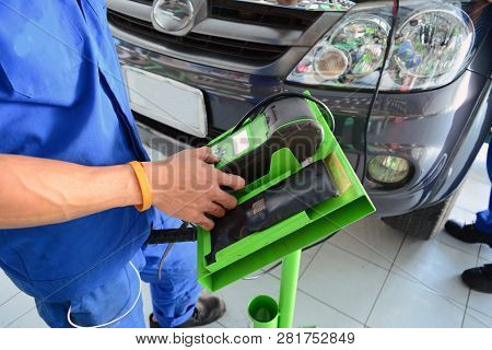 The Mechanic In Blue Uniform Use The Green Battery Testing Tool In Front Of The Grey Car At The Car