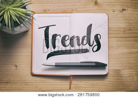 Trends. Trends Concept With A Paper Notebook On The Wooden Desk, Top View.