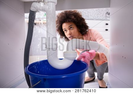 Portrait Of An Young African Woman Looking At Water Leaking From Sink Pipe
