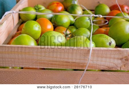Green tomatoes in wood box to background