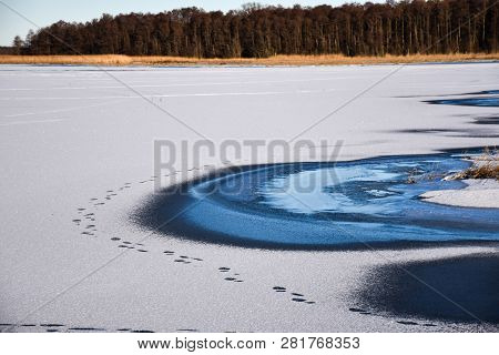 Landscape With A Bright Frozen Lake With Human Footprints