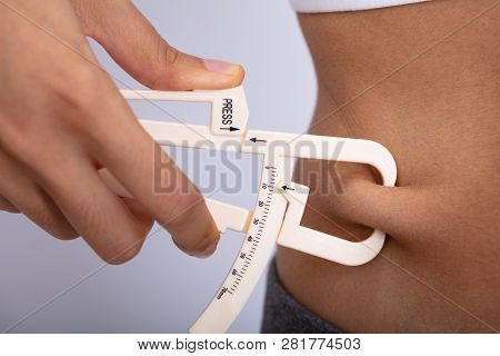Woman Measuring Her Body Fat With Caliper