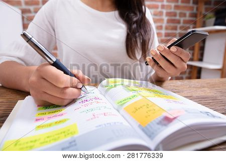 Close-up Of A Businesswoman Holding Cellphone Writing Schedule In The Diary With Pen
