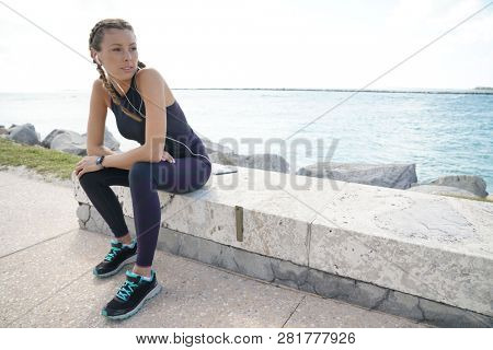 Young sporty woman resting outoors in sun after run