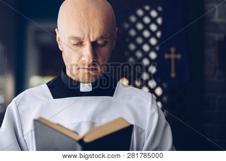Catholic Priest Reading Bible In Church. Faith And Religion