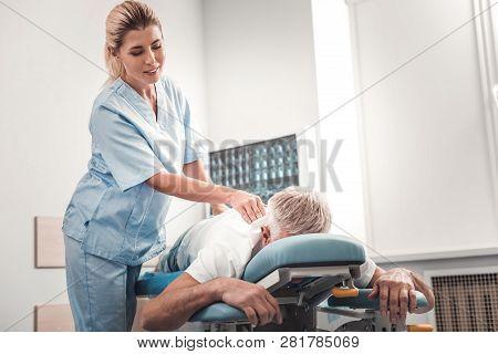 Blonde-haired Chiropractor Checking Spine Of Elderly Man