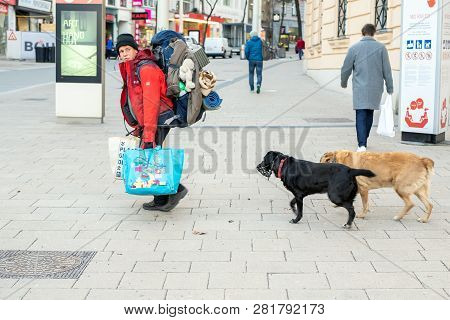 Vienna, Austria - January 16th, 2019: Tramp With Two Dogs Walking On City Street. Travelling Wandere