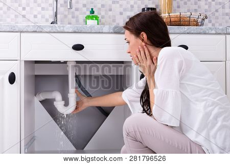Rear View Of A Woman Trying To Stop Water Leakage From Sink Pipe In Kitchen