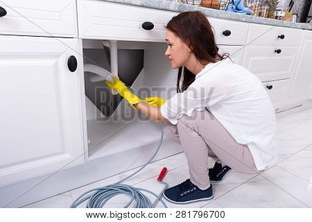 Side View Of A Young Woman Cleaning Clogged Sink Pipe In Kitchen poster