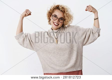 How Strong Girl Is. Portrait Of Enthusiastic Happy And Confident European Blond Woman In Glasses And