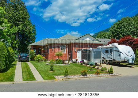 Family House With Traced Driveway And Parked Car On It. Residential House With Rv Parked In Front On