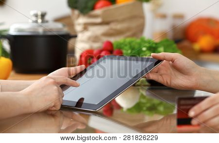 Close-up Of Human Hands Using Tablet Or Touch Pad. Two Women In Kitchen. Cooking, Friendship Or Onli