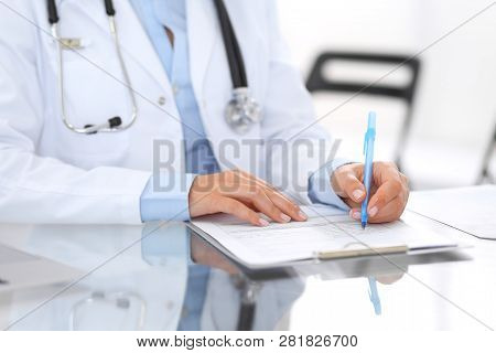 Unknown Doctor Woman At Work, Hands Close-up. Female Physician Filling Up Medical Form While Sitting