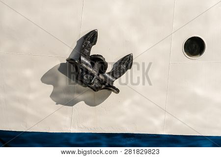 Detail Of A White And Blue Ship Prow With A Black Anchor And A Porthole