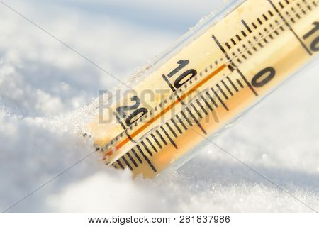Thermometer On Snow Shows Low Temperatures In Celsius.