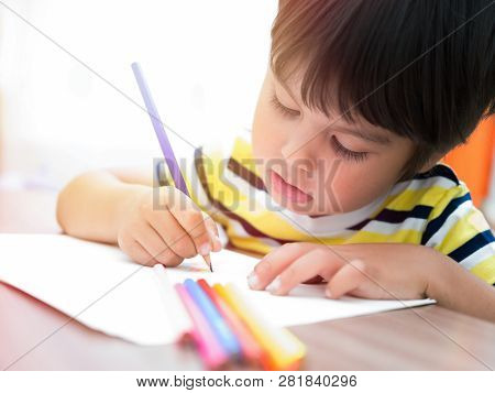 The Child Paints With Colored Pencils On Paper