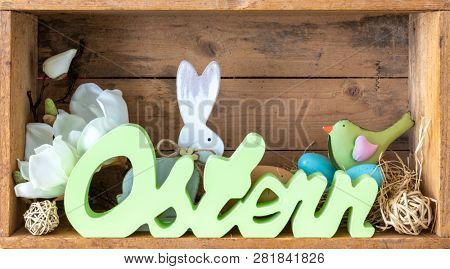 The word easter in german language with decoration in a wooden box