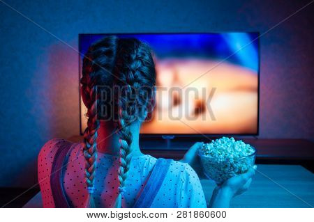 A Young Girl Watching Movies And Eating Popcorn With A Bowl On The Background Of The Tv. The Color B