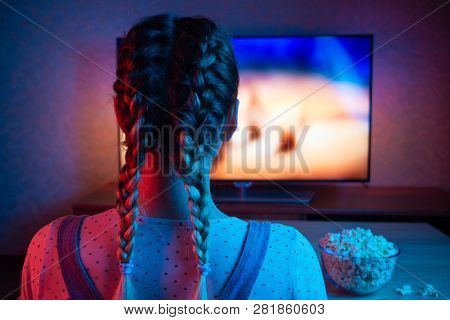 A Young Girl Watching Movies With A Bowl Of Popcorn On The Background Of The Tv. A Bright Color Of L