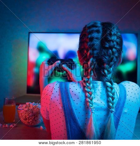 Gamer Or Streamer Girl At Home In A Dark Room With A Gamepad, Playing With Friends Online In Video G