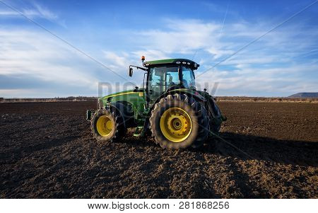 Varna, Bulgaria - March 5, 2017 Ploughing A Field With John Deere Tractor. John Deere Was Manufactur