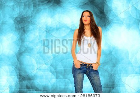 Foto stock de jóvenes, en forma y sexy mujer en jeans y blanco sobre fondo azul bokeh