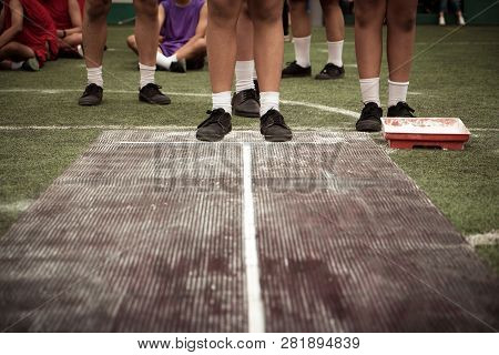 Students Boy Taking Long Jump On Rubber Board Pid Or Sand Pid During A School Sport Competition Day.