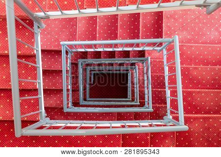 Top View In Symmetric Stairwell With Red Carpet And Steel Parapet