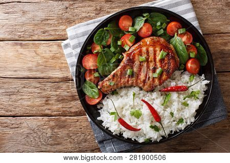 Grilled Pork Steak With Rice Garnish And Fresh Vegetable Salad Close-up. Horizontal Top View
