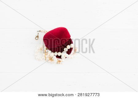 Overhead View Of Opened Red Gift Jewellry Box With Necklace Of Pearls On White Wooden Background Wit